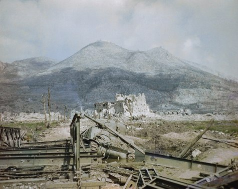 1280px-The_ruins_of_Cassino,_May_1944-_a_wrecked_Sherman_tank_and_Bailey_bridge_in_the_foreground,_with_Monastery_Ridge_and_Castle_Hill_in_the_background._TR1799